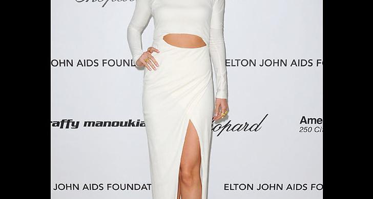 ... visar upp hud i sin vita klänning.