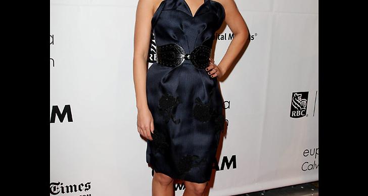 ... matchar sin mörkblå klänning med accessoarer i svart.