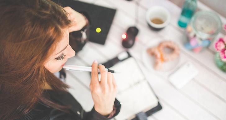 En bild ovanifrån på en tjej som sitter vid ett skrivbord och fyller i sin almenacka.