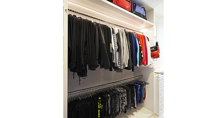 Träningsbyxor och jackor hänger perfekt uppradat i denna garderob.