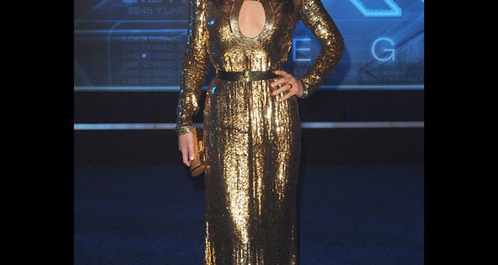 ... klär sig i guldfärgad sci fi-inspirerad klänning.