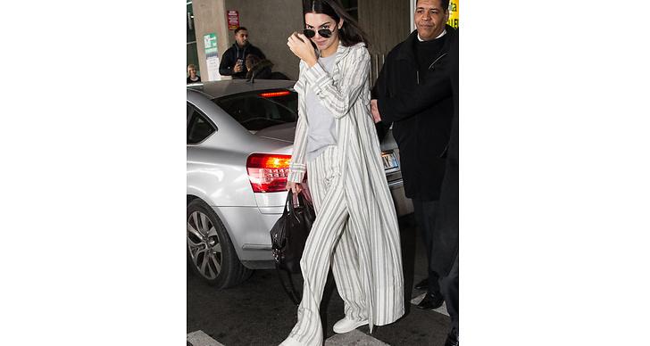 Kendall reser med stil! Här i ett randigt set och som hon matchar med bekväma sneakers.