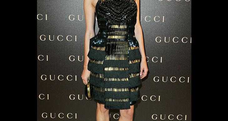... har på sig en klänning med detaljer i metall.
