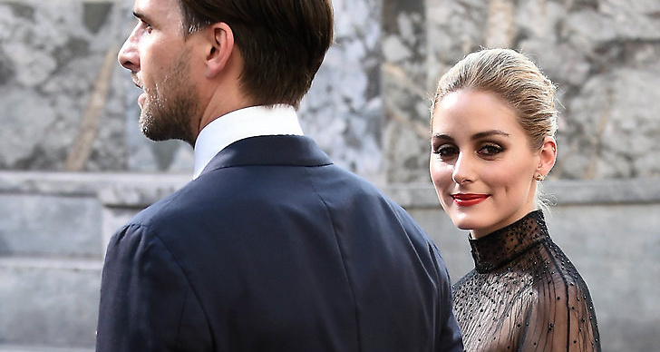En tjej som kollar in i en kamera och ler, bredvid henne står en man.
