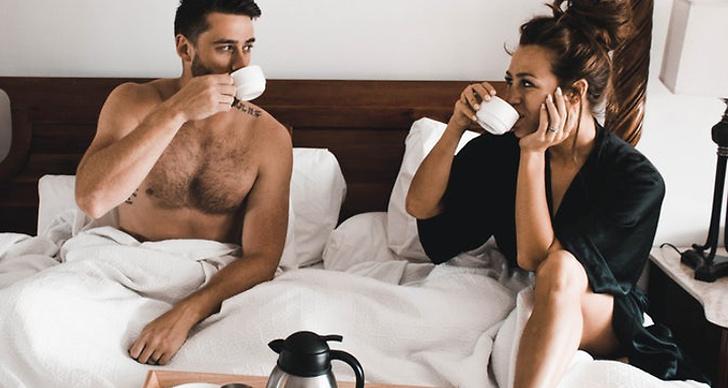 En kille och en tjej dricker kaffe i en säng.