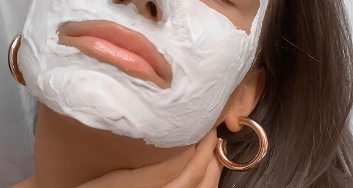 En närbild på kvinna med ansiktsmask och runda, tjocka örhängen.