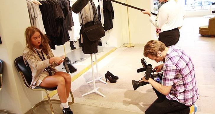 Angelica provar ett par skor framför kameran.