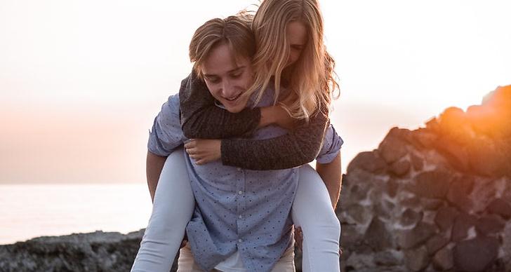 En tjej som sitter på en killes rygg